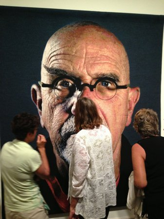 Visitors admire a self-portrait at the opening
