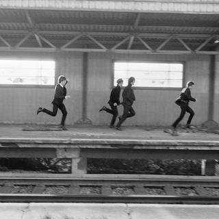 ENGLAND. LONDON. The BEATLES during filmng of 'A Hard Days Night'. The Beatles film was primarily shot on a moving train. The four Beatles running on train platform. art for sale