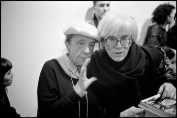 Louise Bourgeois and Andy Warhol (holding my book), New York, 1987., by Inge Morath